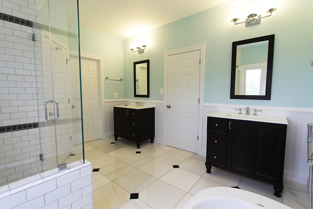 Dark Vanity, Marble Floors, Wainscot, Frameless Shower Door