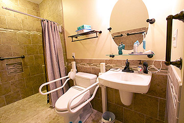 Handicap bathroom remodel with curbless oversized shower, low shower niche, swivel shower curtain rod, multiple grab bars, handicap accessable vanity sink by Ramcom Kitchen and Bath